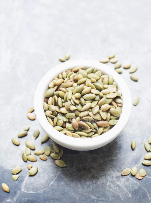 Cerca de las semillas de calabaza en un recipiente - foto de stock