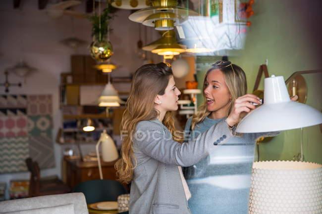 Mujeres amigas de compras en tienda de iluminación - foto de stock