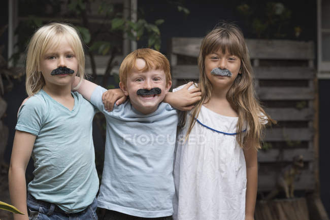 Crianças em bigodes falsos, sorrindo para a câmera — Fotografia de Stock
