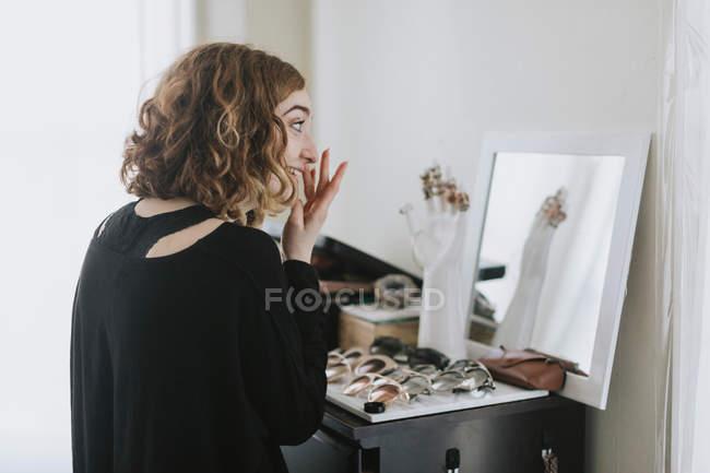 Seitenansicht einer Frau am Schminktisch — Stockfoto