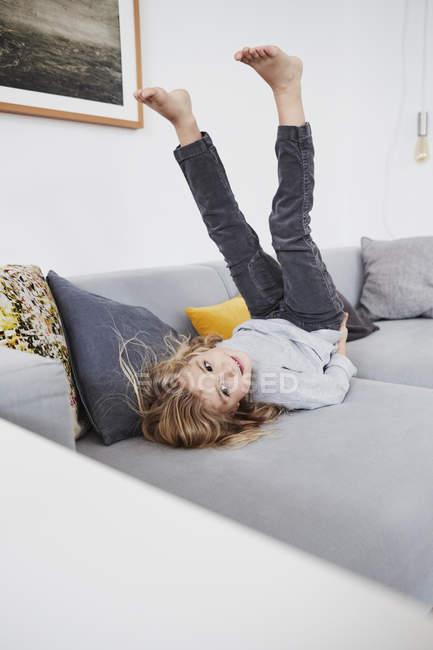Молодая девушка, лежа на диване с ногами в воздухе — стоковое фото