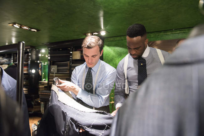 Tailor and customer looking at unfinished bespoke jacket in traditional tailors shop — Stock Photo