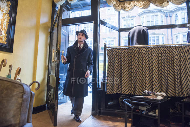 Male customer in winter coat and trilby arriving in tailors shop — Stock Photo