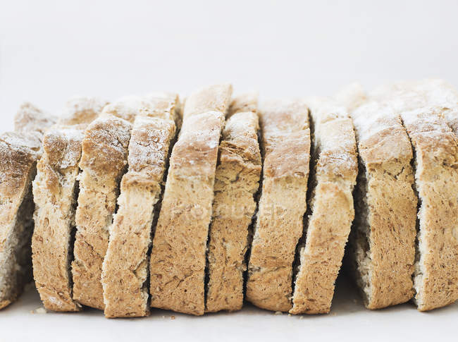 Whole grain oat bread slices on white surface — Stock Photo