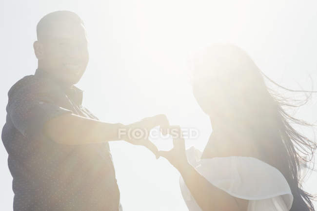 Portrait of couple outdoors, hands touching, making heart shape — Stock Photo