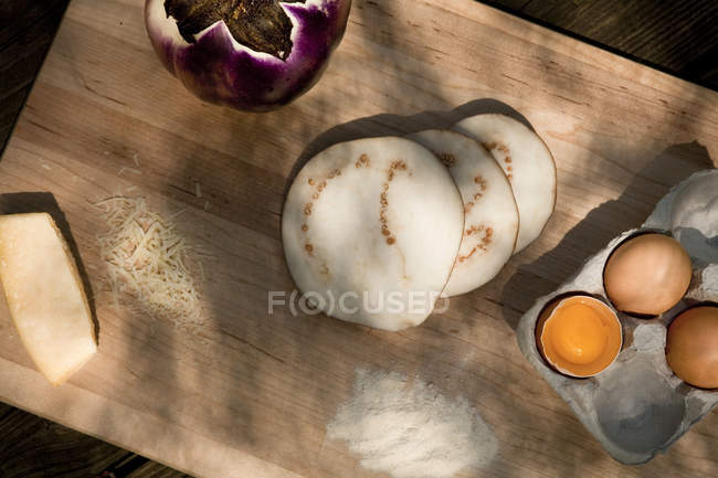 Eggs, cheese and slices of eggplant on wooden board — Stock Photo