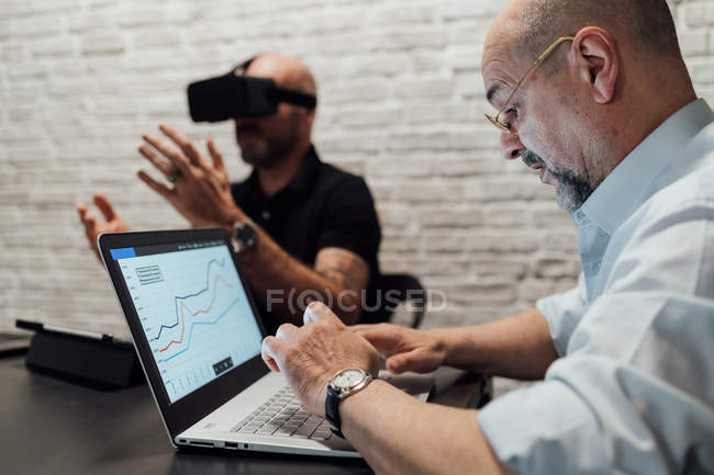 Коллеги, работающие с гарнитурой виртуальной реальности и ноутбуком — стоковое фото