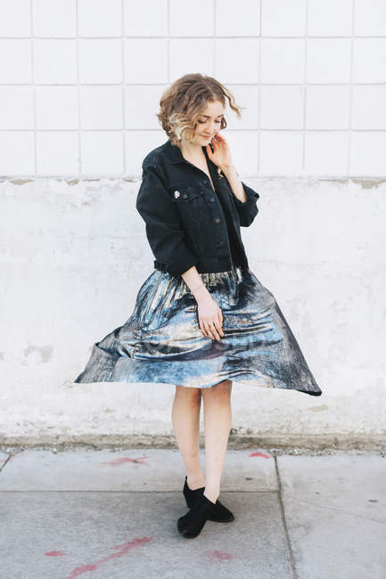 Woman in street twirling metallic skirt against wall — Stock Photo