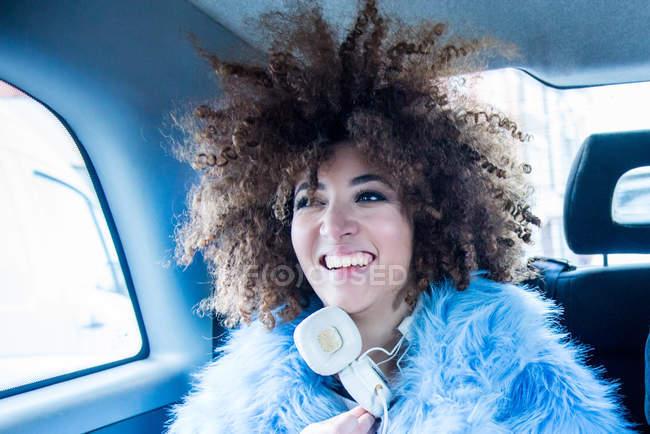 Ritratto di giovane donna sorridente sul retro del taxi — Foto stock