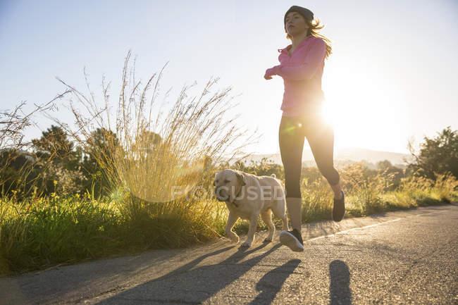 Молодая женщина бежит по сельской дороге с собакой — стоковое фото