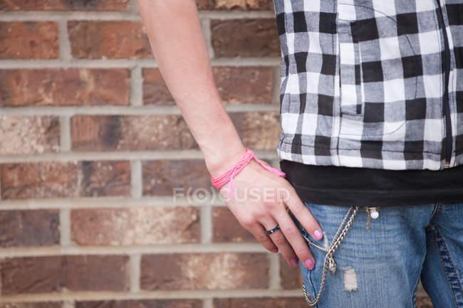 Женщина, носить проверяемый черно-белый топ кирпичная стена — стоковое фото