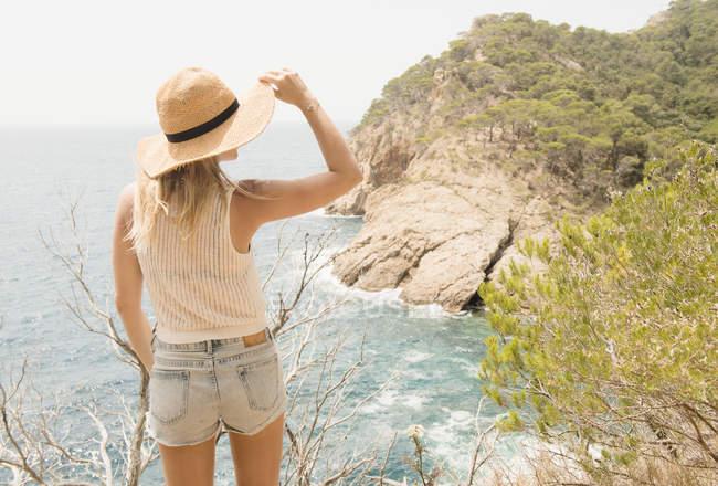 Vista posteriore della donna sulla costa guardando la vista, Tossa de mar, Catalogna, Spagna — Foto stock