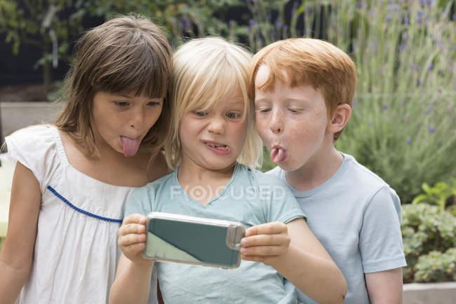 Kinder Zungen herausragen und nehmen selfie — Stockfoto