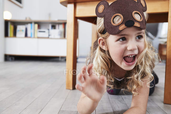Young girl crawling under table in bear mask — Stock Photo