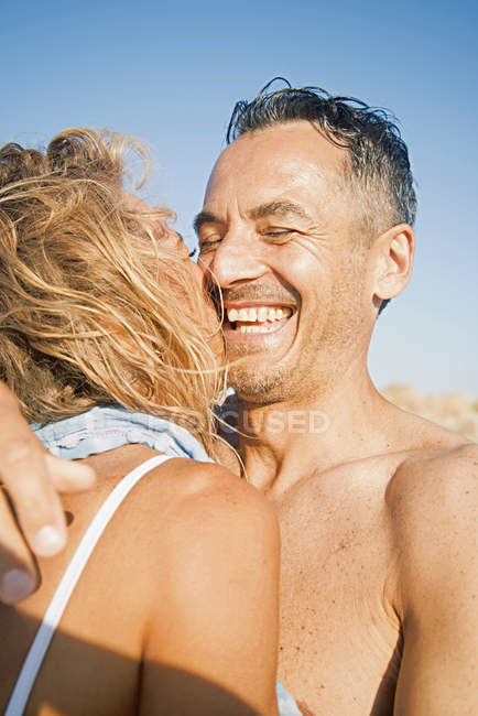 Mature couple in swimwear hugging on beach — Stock Photo