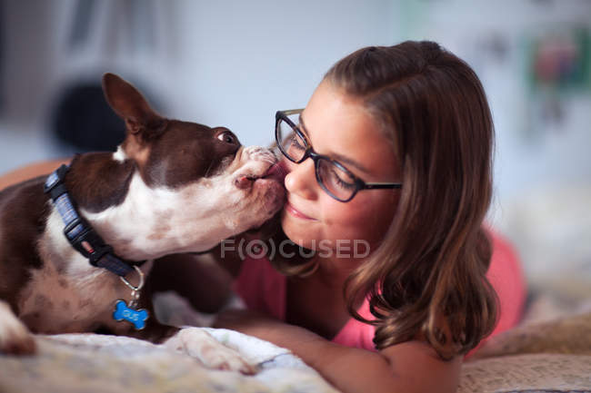 Girl lying on bed with pet dog — Stock Photo