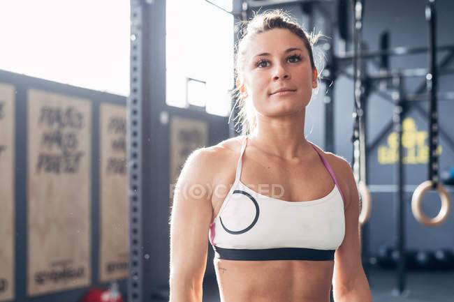 Portrait of woman in gym smiling at camera — Stock Photo