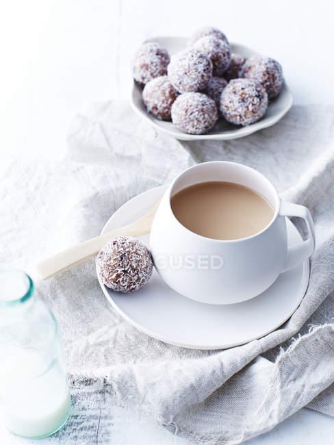 Vue rapprochée de lait, de cacao et de délicieuses boules de canneberge sur table — Photo de stock