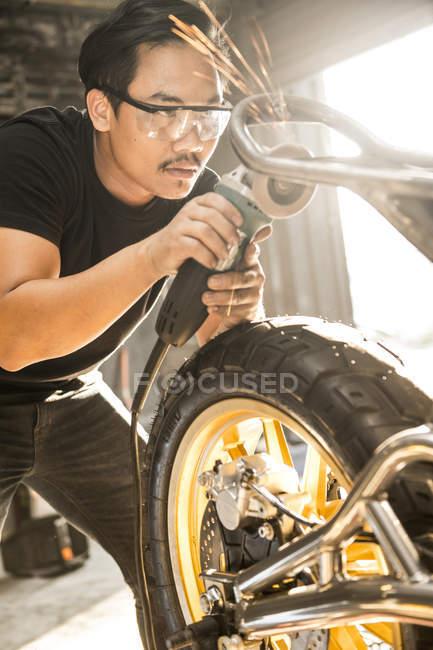 Mechanic working with power tool at custom motorbike shop, Bangkok, Thailand — Stock Photo