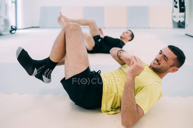 Dabei Sit Mann USV in Turnhalle — Stockfoto