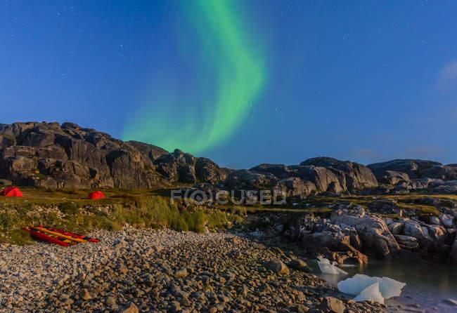 Paisaje con tiendas de campaña por el fiordo y aurora boreal por la noche, Narsaq, Vestgronland, Groenlandia del sur - foto de stock