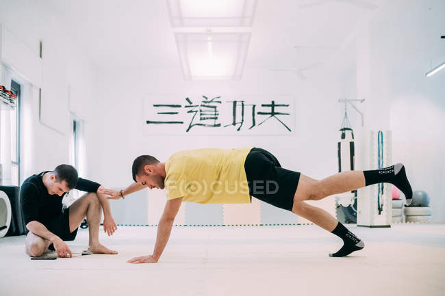 Man with coach doing push ups — Stock Photo