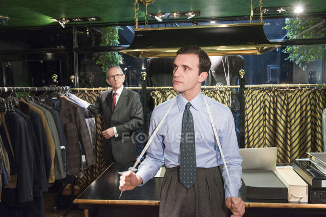 Tailor with tape measure around neck in tailors shop — Stock Photo
