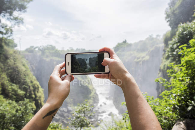Young female tourist taking smartphone photographs of Victoria Falls, detail of hands, Zimbabwe, Africa — Stock Photo