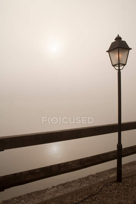 Lamp post by wooden fence near foggy lake at night — Stock Photo