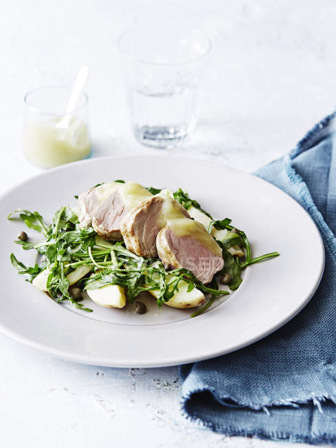 Pork with kipfler potatoes and apple sauce, on white plate, close-up — Stock Photo