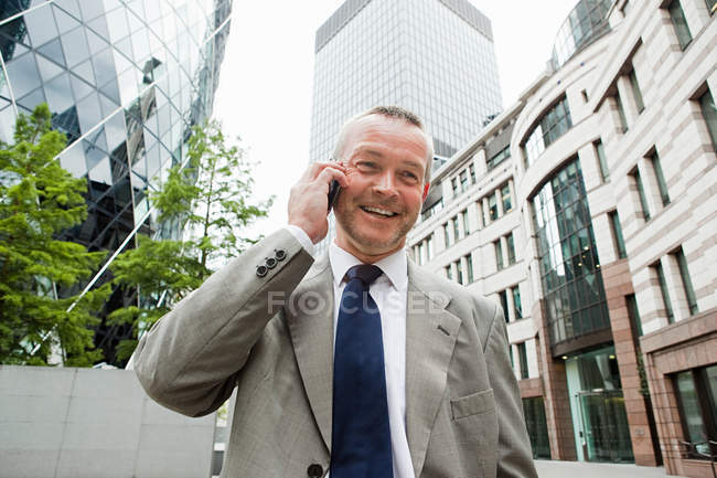 Businessman talking on cellphone and office buildings at background — Stock Photo