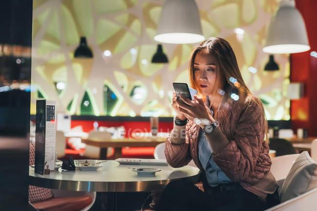 Жінка, сидячи в ресторані і за допомогою смартфона — стокове фото