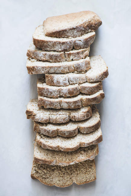 Elevated view of freshly baked loaf of bread cut into slices — Stock Photo