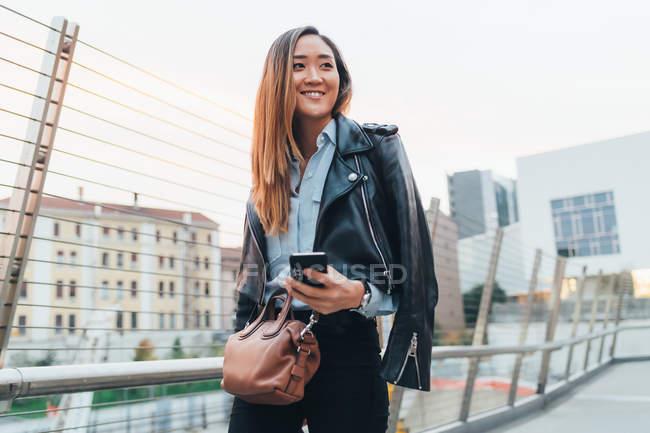 Donna d'affari che cammina con lo smartphone in mano — Foto stock