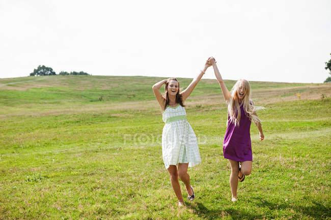 Молодые женщины, пропуская через поле с поднятыми — стоковое фото
