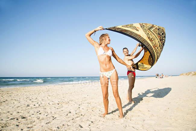Зрелая пара на пляже держит пляжное одеяло — стоковое фото