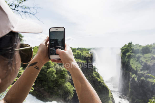 Back view of Young female tourist making photos with smartphone of Victoria Falls, Zimbabwe, Africa — Stock Photo