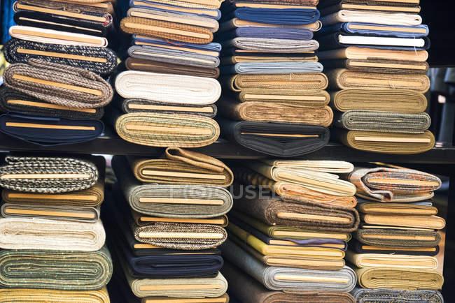 Pilhas de pano enrolado na loja tradicional alfaiates — Fotografia de Stock