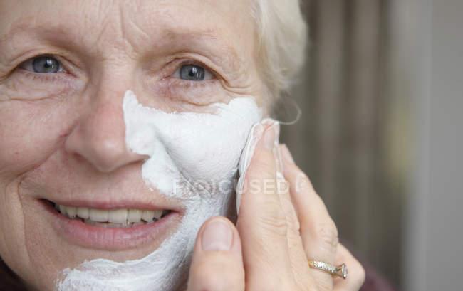 Primo piano della donna anziana che applica maschera facciale — Foto stock