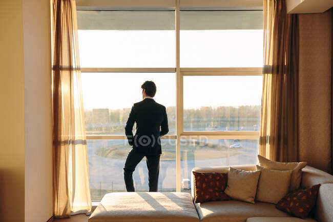 Businessman looking out of hotel bedroom window — Stock Photo