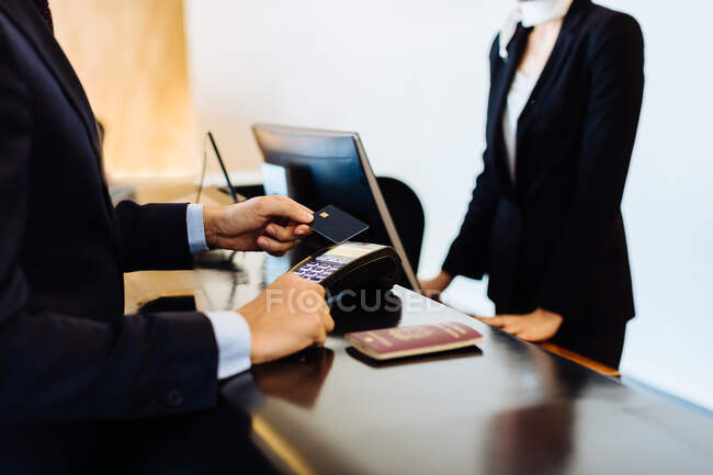 Бізнесмен робить безконтактну оплату на прийомі в готелі. — стокове фото