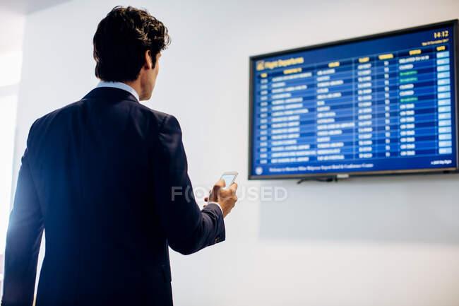 Бизнесмен проверяет вылет — стоковое фото