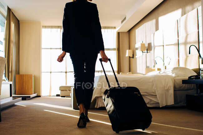 Businesswoman with wheeled luggage in hotel bedroom — Stock Photo