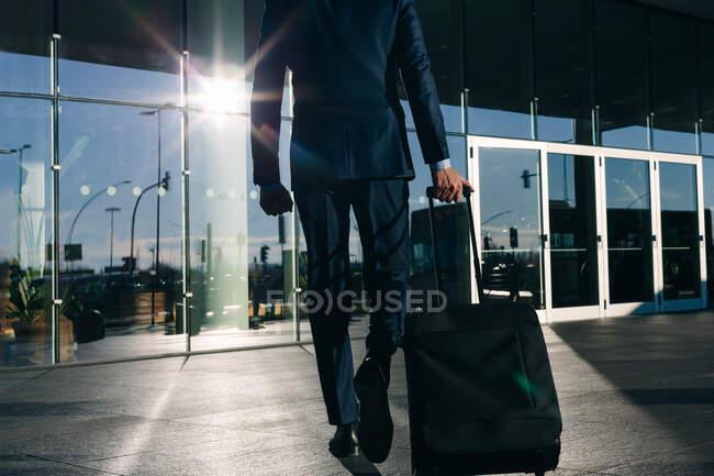 Бизнесмен с колесным багажом, проезжающий мимо стеклянного здания, Мальпенса, Милан — стоковое фото