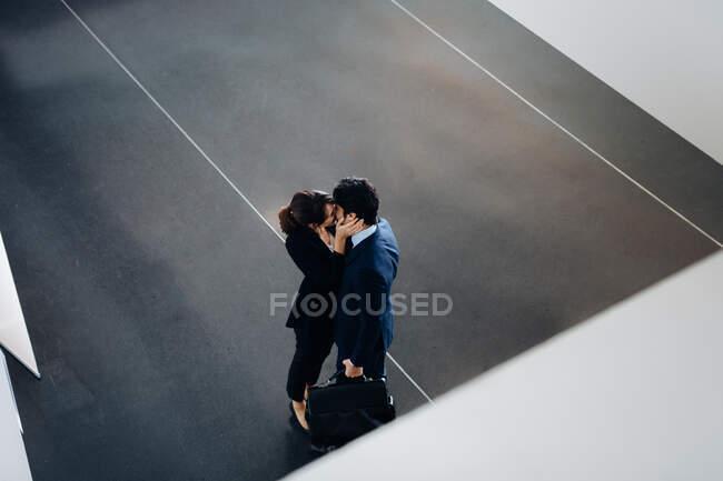 Couple en costumes d'affaires baisers — Photo de stock