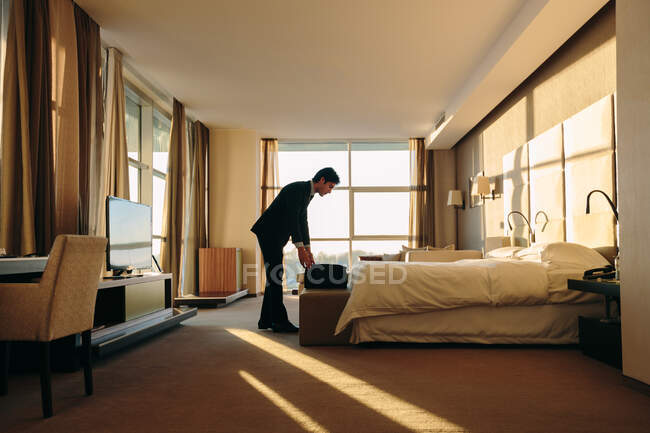 Empaquetador de equipaje en el dormitorio del hotel - foto de stock