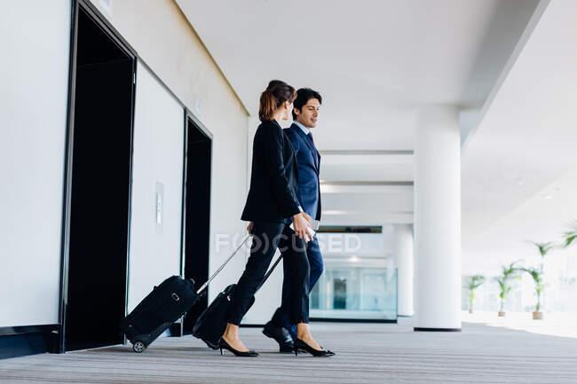 Uomo d'affari e donna d'affari con bagagli a ruote in uscita scale mobili dell'hotel — Foto stock