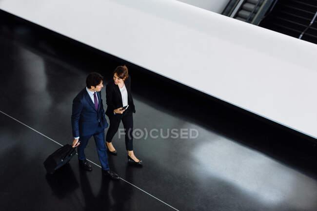 Uomo d'affari e donna d'affari con bagaglio a ruote nell'edificio dell'hotel — Foto stock