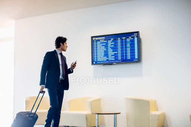 Businessman with wheeled luggage checking departure board — Stock Photo