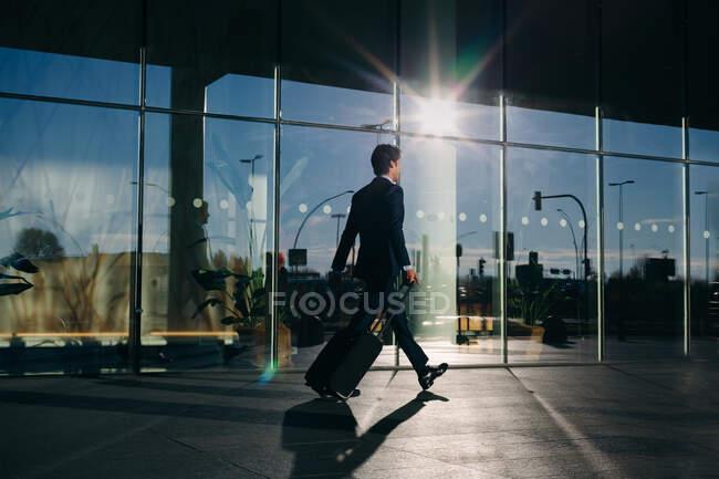 Businessman with wheeled luggage passing glass building, Malpensa, Milan — Stock Photo